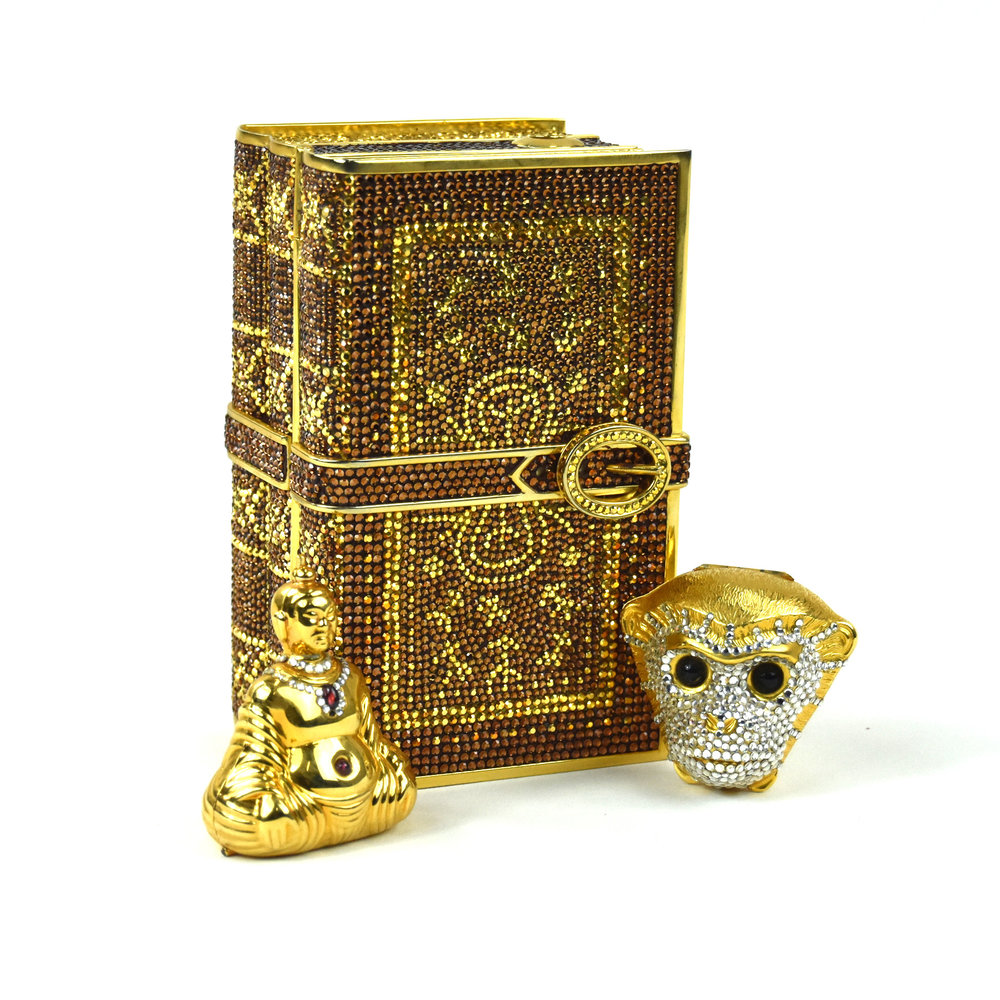 Bronze and gold crystal book clutch, 1991; Tutankhamen monkey head pill case, 1989; Buddha pill case 1987