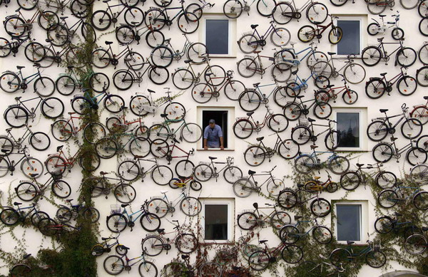 A bicycle shop in Altlandsberg, Germany advertises their goods with a wall of around 120 bikes mounted on the building's exterior in lieu of a sign.
