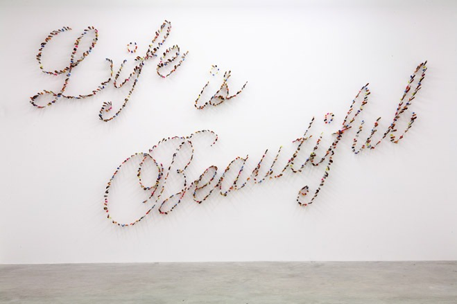 """Life is beautiful"" by Farhad Moshiri. Made from hundreds of knives stabbing the walls."