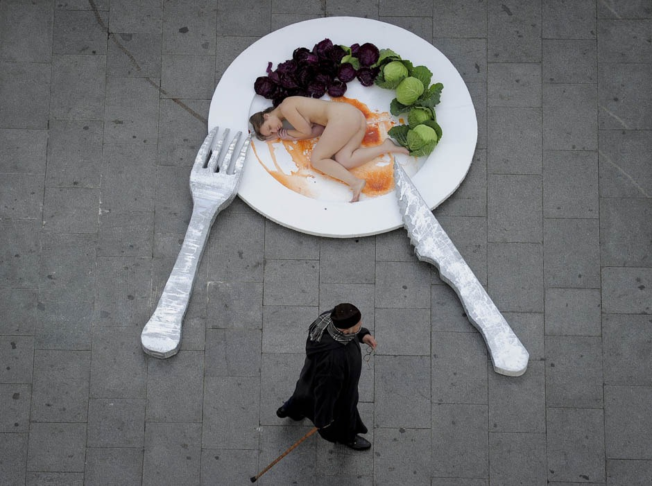 "An activist of the animal-rights group ""AnimaNaturalis"" lays down naked on a giant plate of food during a performance to denounce the consumption of meat on December 15, 2011 in the center of Barcelona, Spain."
