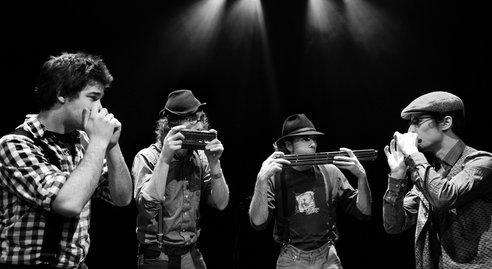 """D'Harmo  is strictly composed of harmonica players. This type of band rarely seen and heard truly offers a one-of-a-kind show.  D'Harmo  performs an original roster of songs composed by its members and played using various types of harmonicas. The harmonicists :  Pascal """"Per"""" Veillette ,    Samuël Caron ,  Cédric Houdayer  and  Lévy Bourbonnais  are among the most talented in Canada. Their music inspired from Klezmer, Quebec folklore, jazz and classical music combines modernity and tradition, eclecticism and pop.   """"Four harmonica players harmonize and improvise brilliantly across Jewish traditions, jazz, rag, minimalist music, minuet, waltz, tango, reel and beyond. But this foursome always expands on the original form of the genres it leverages. Then there is blowing, breathing, the exchange of roles and the instruments . . . The music swings and wails, ultimately influenced by dance tunes of the 2010s for big finishers. The combination is lush.""""   www.dharmo.ca"""