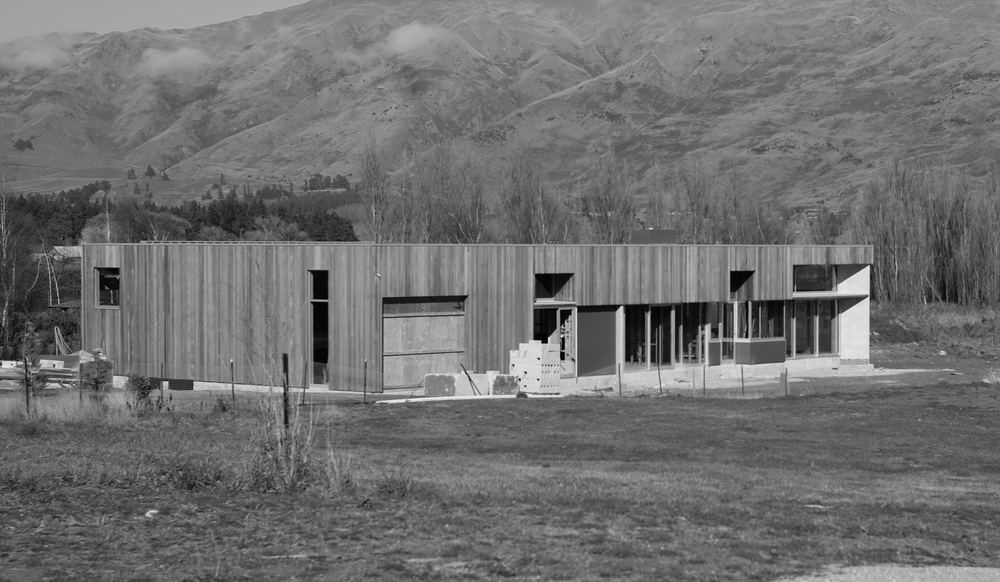 "Wanaka Bach with opaque ""party wall"" progressively eroded towards outer corner and views."