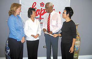 Diana Cohen-Chan, Kapok's managing director, second from left, and Meiling, right, present a cheque to Justice Ulric Cross, director of the Cotton Tree Foundation, while administrator Patricia Gartland looks on.