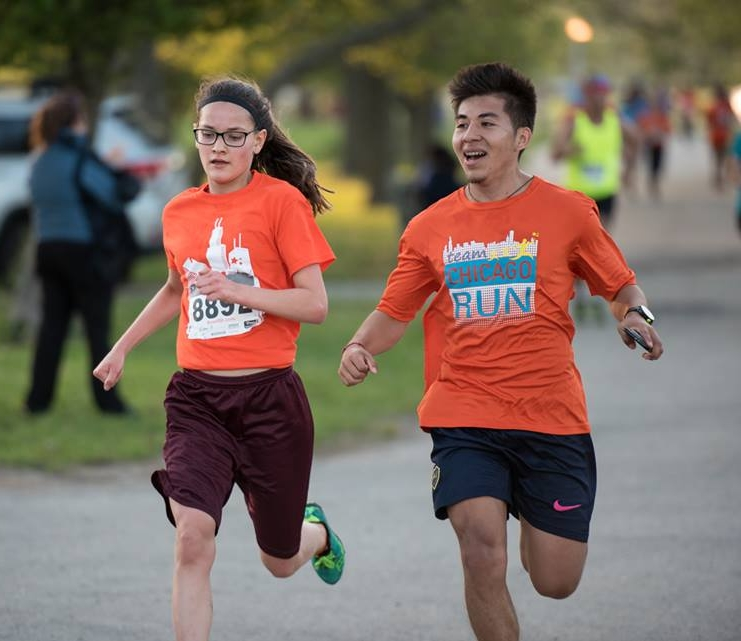 Christian running with a Running Mates student at the 4-Mile Classic race on May 18, 2017