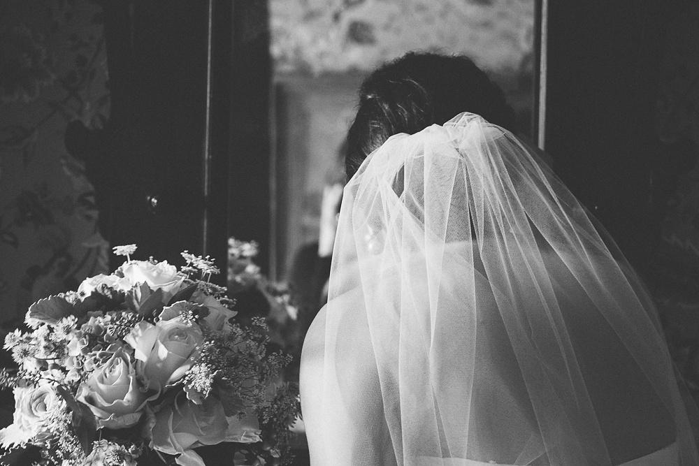 Bride checks her make up at a wedding at The Briars.