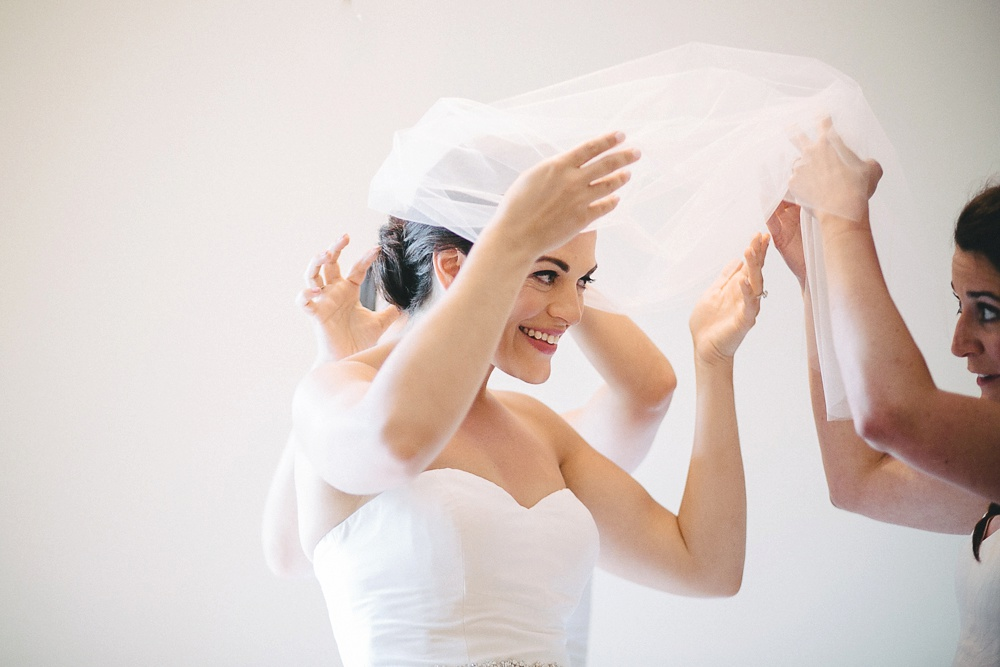 Bridesmaids help bride put veil on as she smiles.