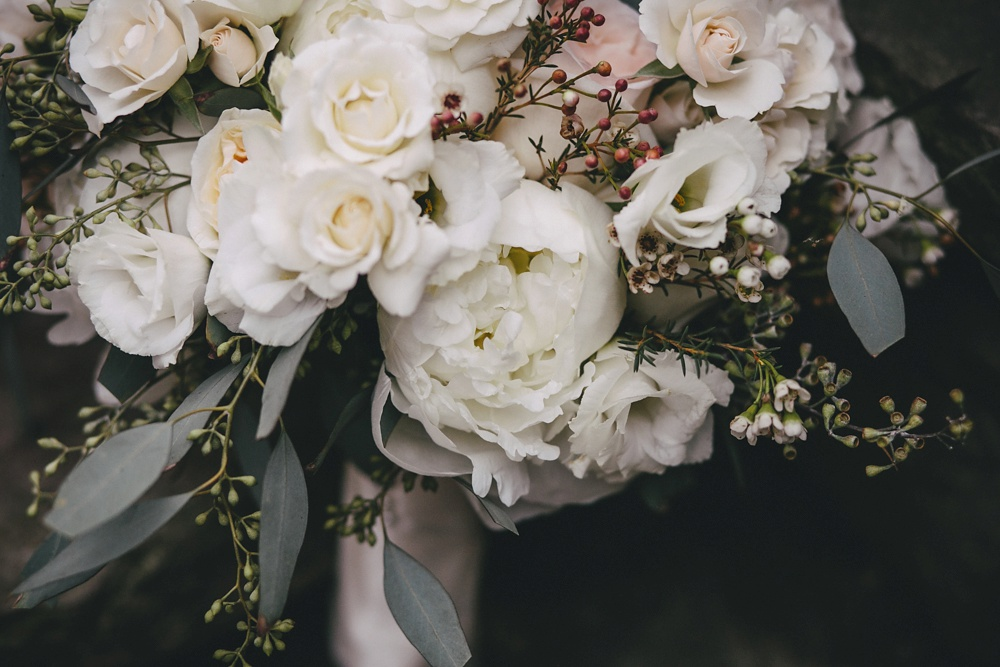 Winter bridal bouquet of mostly white flowers.