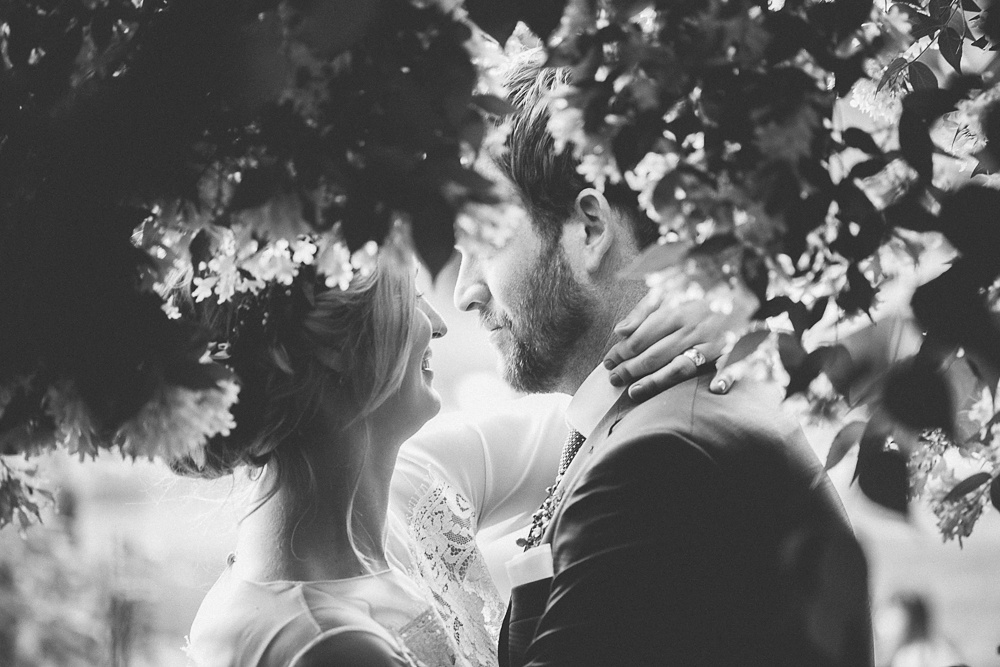 Couple embrace inside a flower bush on their wedding day.