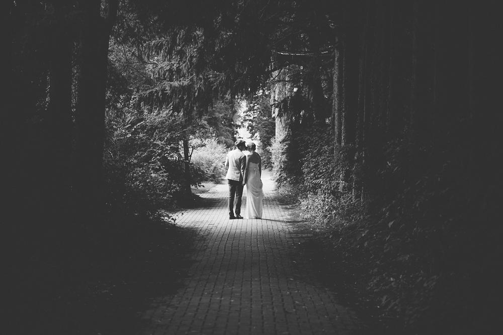 Couple kiss amidst trees on Toronto Island on their wedding day.