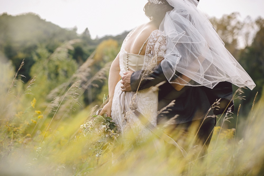 Couple embrace in the blowing tall grass at Brickworks Toronto.