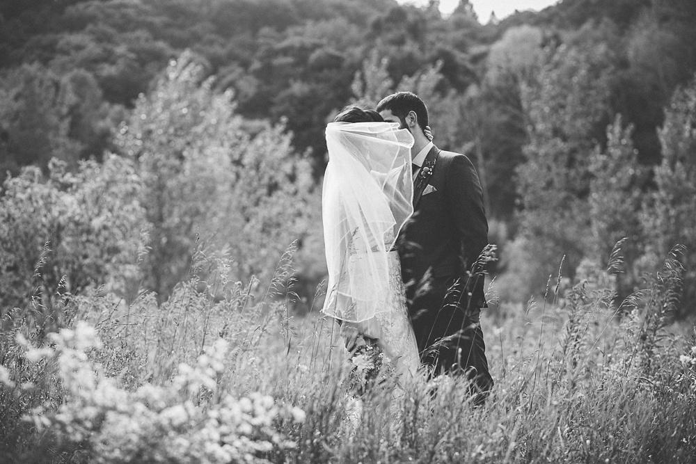 Couple kiss behind a veil at Brickworks Toronto.