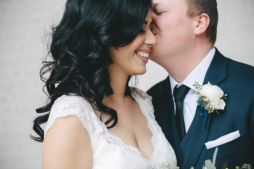 Groom kisses bride on their wintery wedding day.