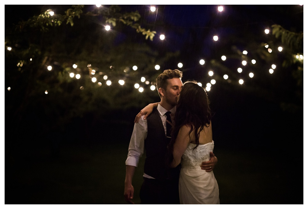 24-DanijelaWeddings-KurtzOrchards-Niagaraonthelake-wedding-couple-rain-kiss-twinklelights.JPG