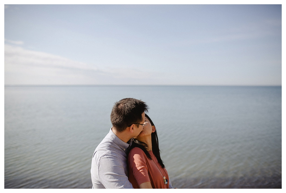 Their love expressed by a kiss in their beach time engagement photo shoot.