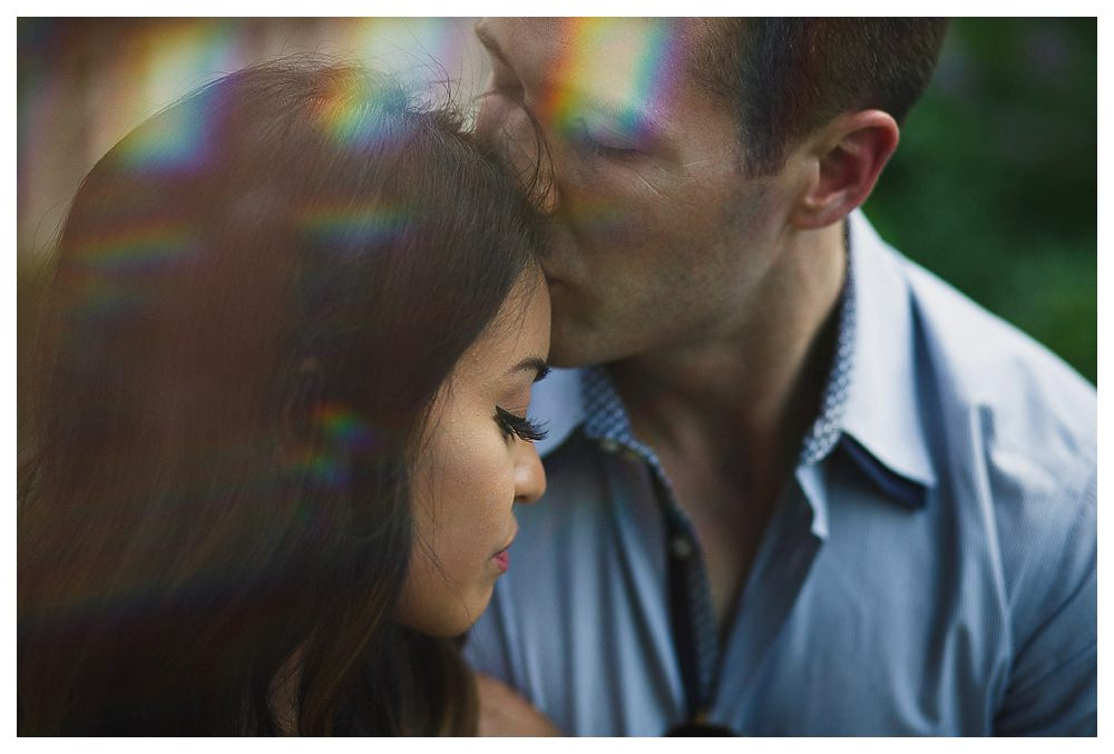 As the sun streaks through the sky, the bride and groom kiss on their engagement photo day
