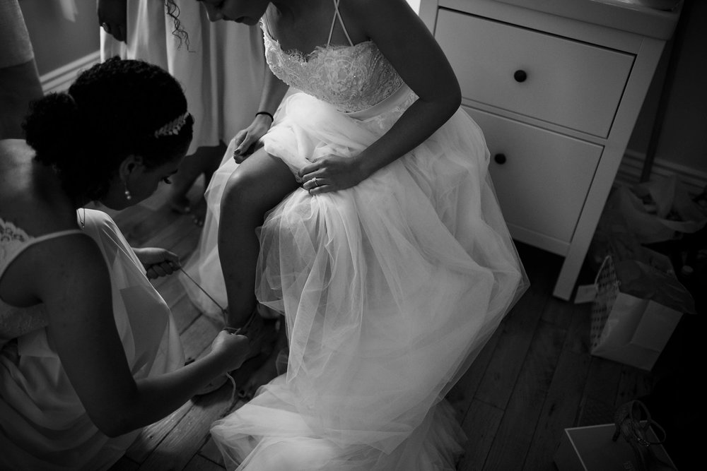 Bride putting on shoes at Gladstone Hotel Toronto wedding.