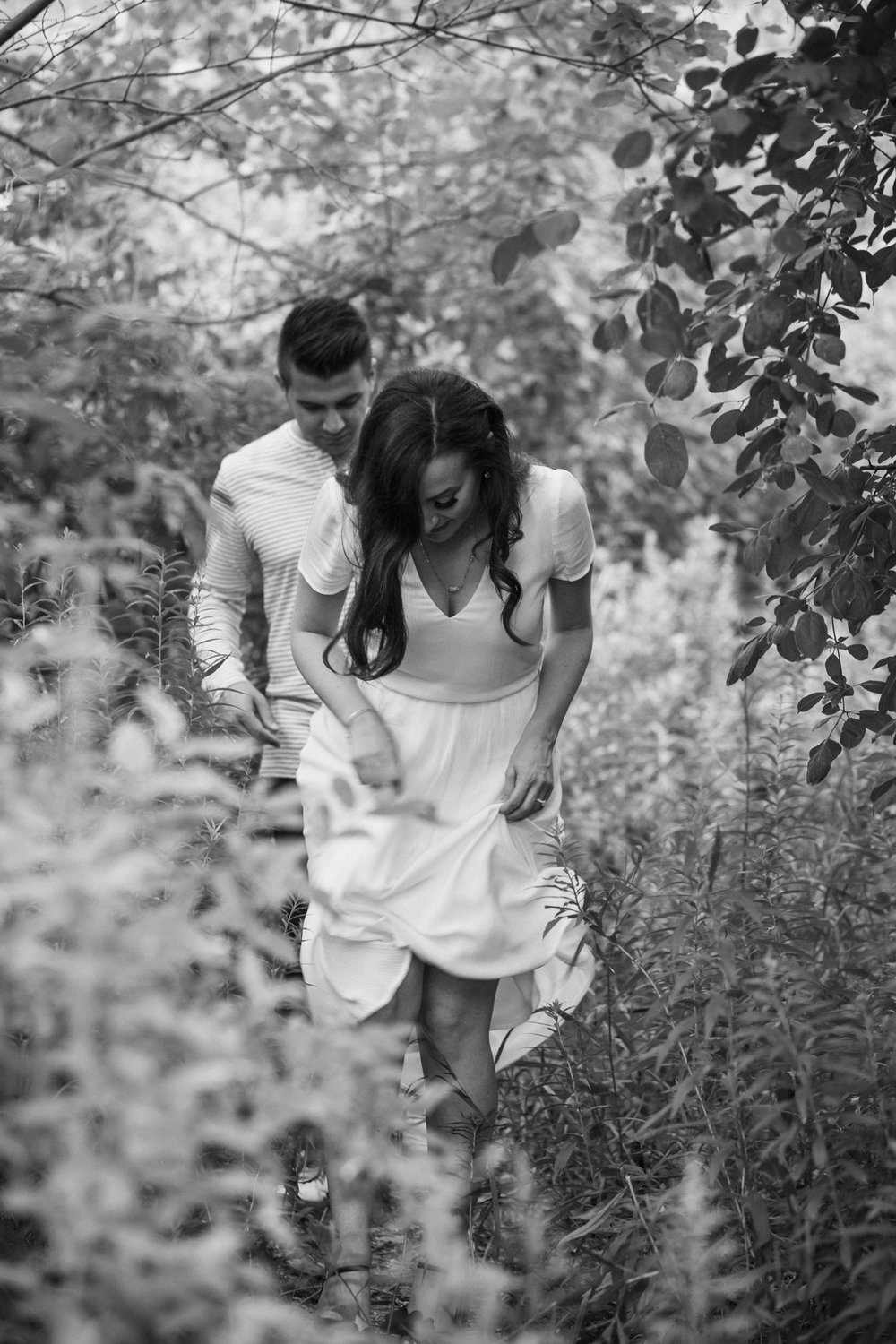 Engagement photography at Cherry Beach Toronto couple walking through woods.