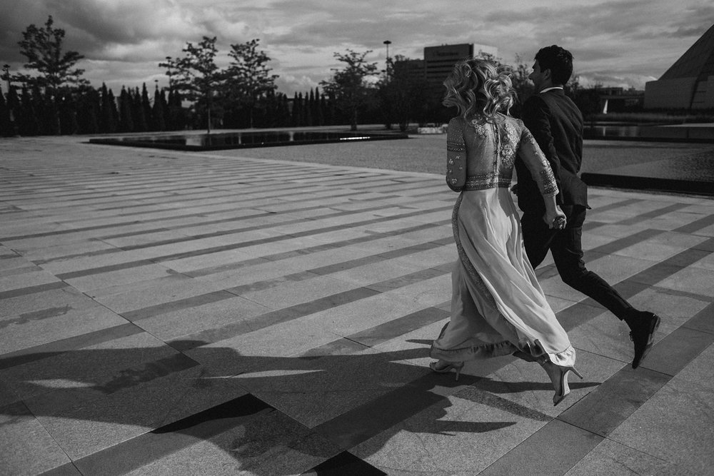 Couple running at Aga Khan engagement photos.