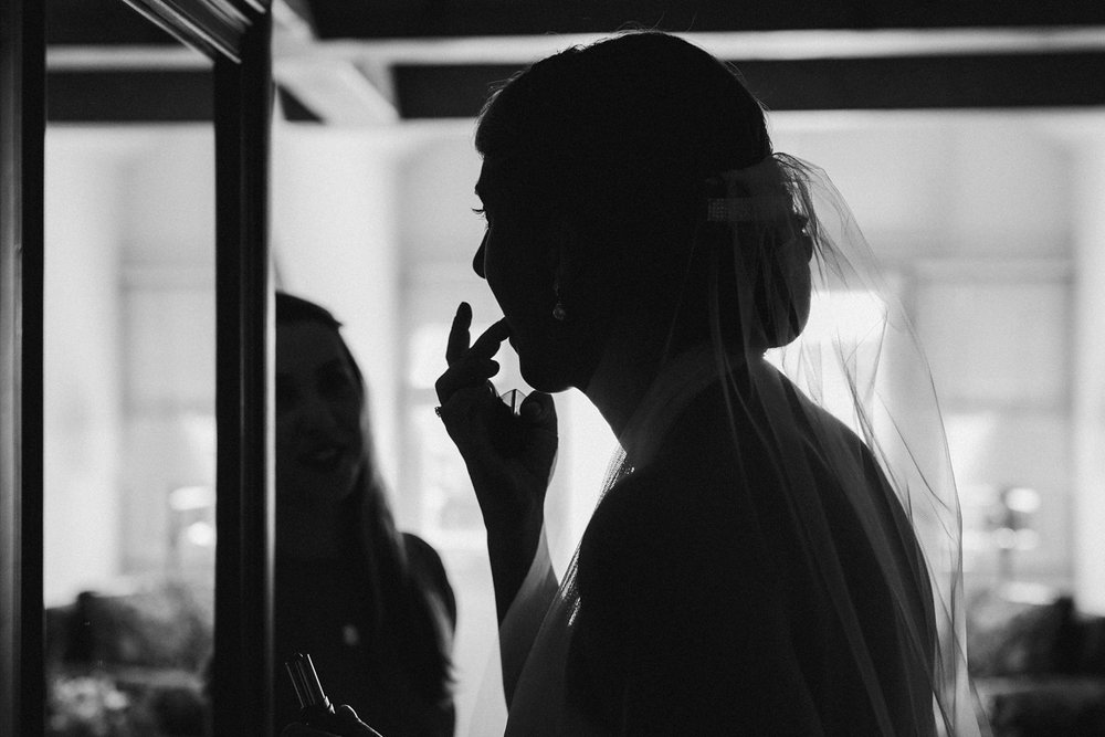 Bride putting make up for wedding in Vermont.