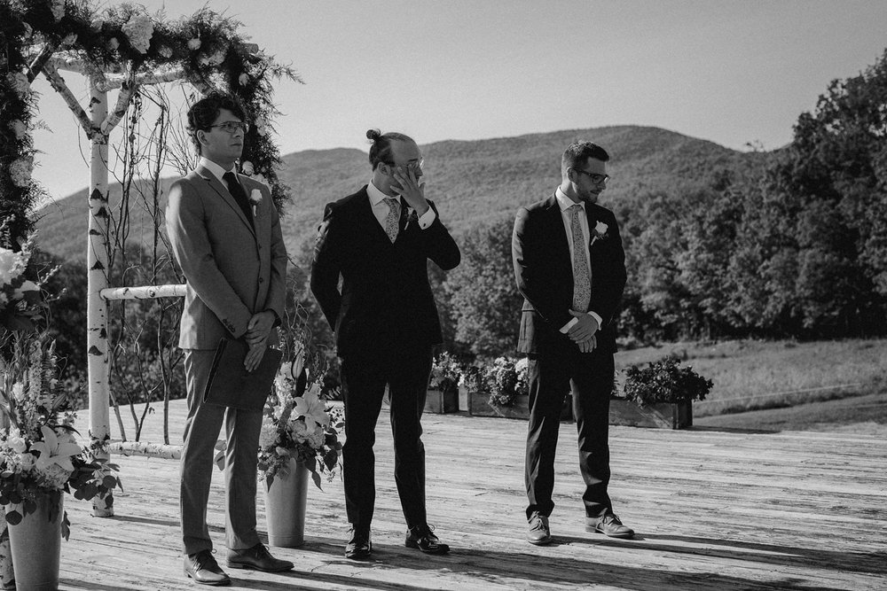 Groom wipes tears at Vermont wedding.