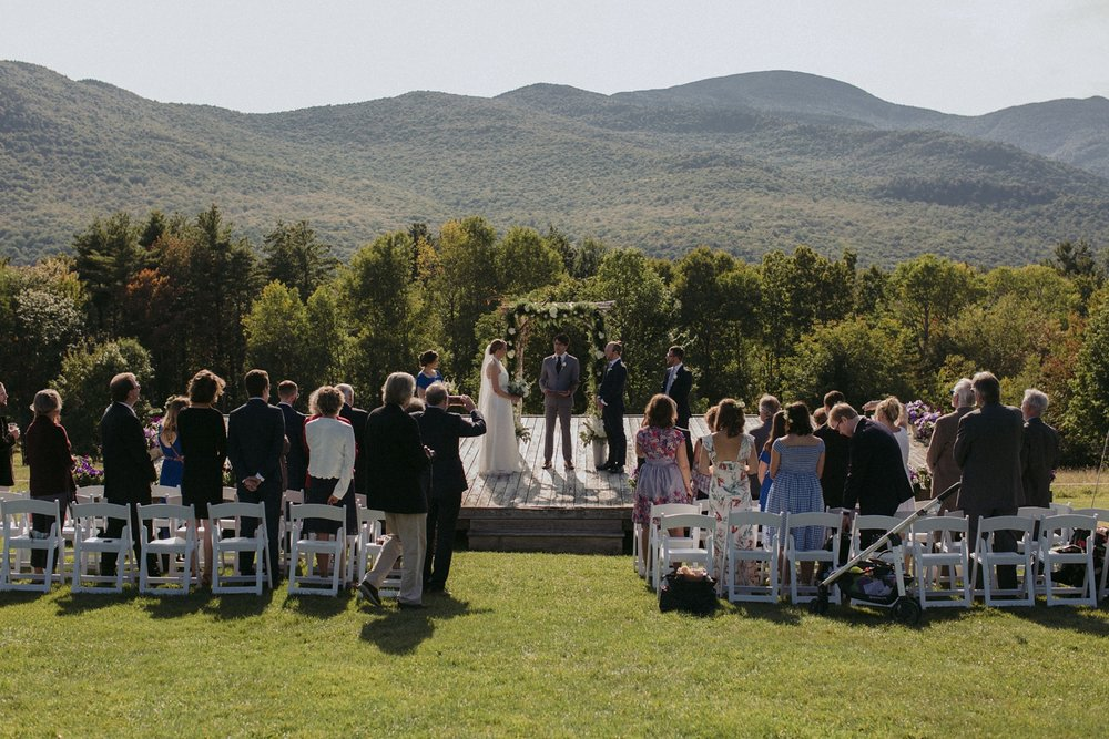 Ceremony in meadow under Vermont hills for destination wedding.