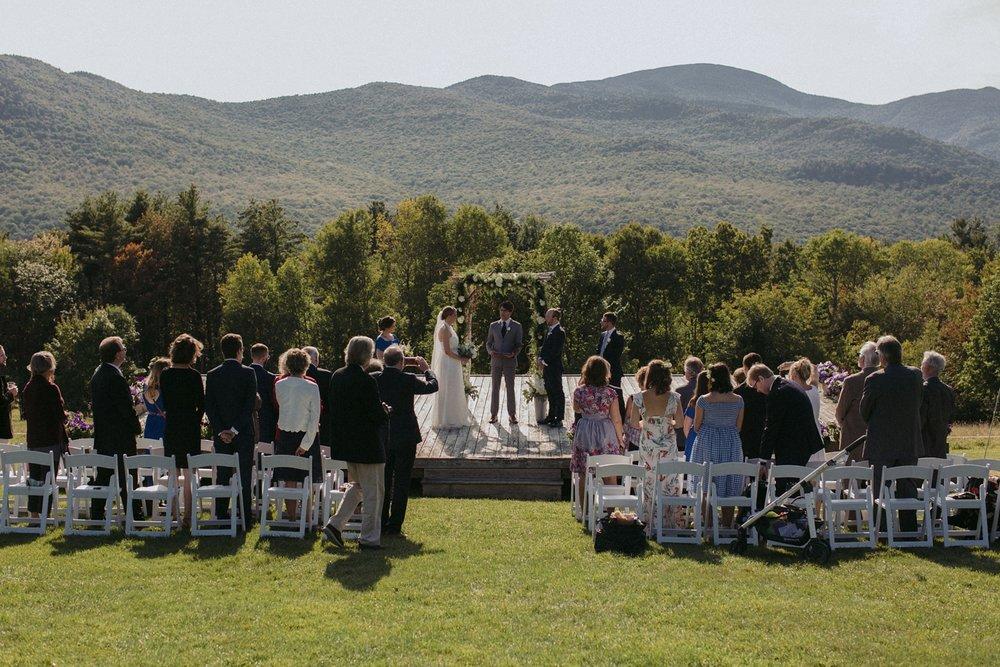 Ceremony in meadow under Vermont hills for destination wedding.