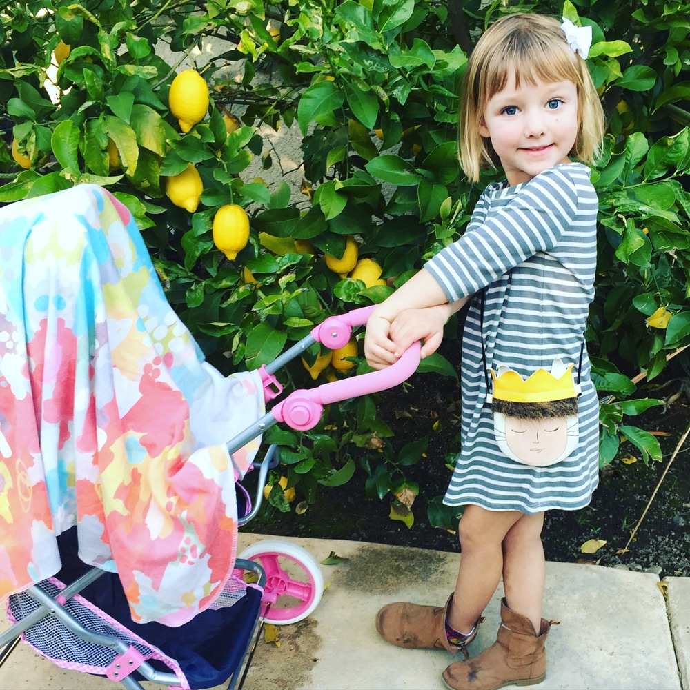 Little mama helping me pick lemons from our back yard, while she takes care of her baby.. busy girl.
