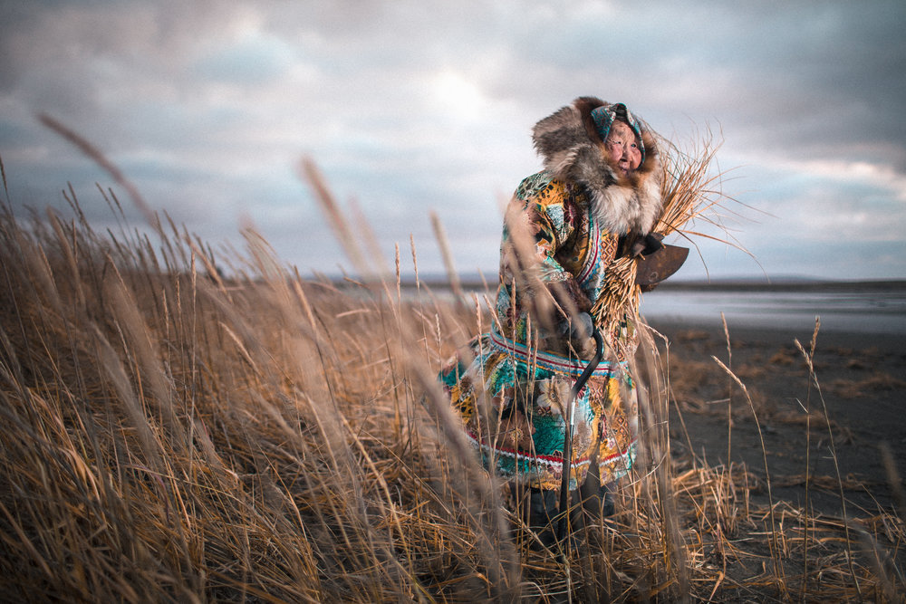 Ida Wesley, the eldest resident on the island, collects grass to be turned into a basket. Ida serves as an important bridge between two worlds, arching gracefuly over the divide where tradition and modernity collide.  [Nunivak Island, Alaska]