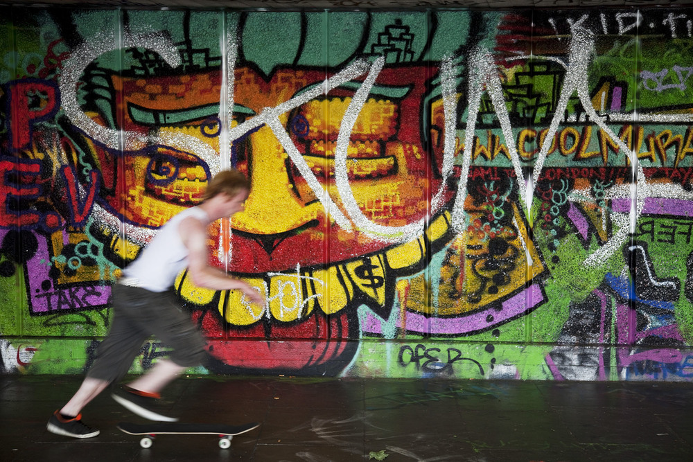 Skateboarder at the South Bank Undercroft passes some graffiti. This is the home of British skating.