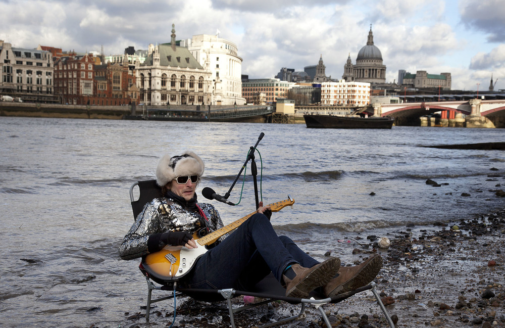 Busker called the 'Flame Proof Moth' performs on the edge of the River Thames in Winter.