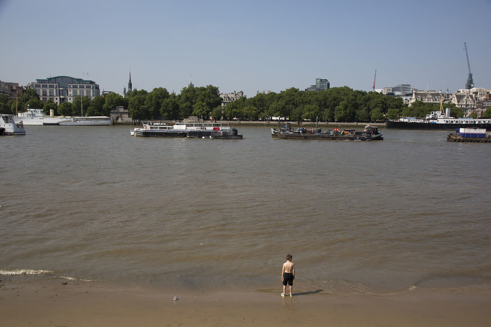 A young boy stands at the edge of the River Thames on the South Bank beach.