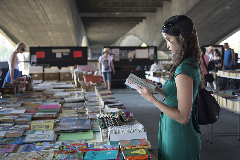 Woman stands engrossed reading a book at the second hand book stalls under Waterloo Bridge.