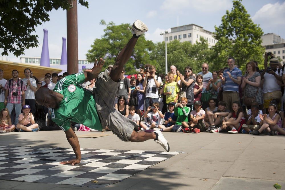 Break dance group One Motion Crew perform for money to a busy crowd of tourists.