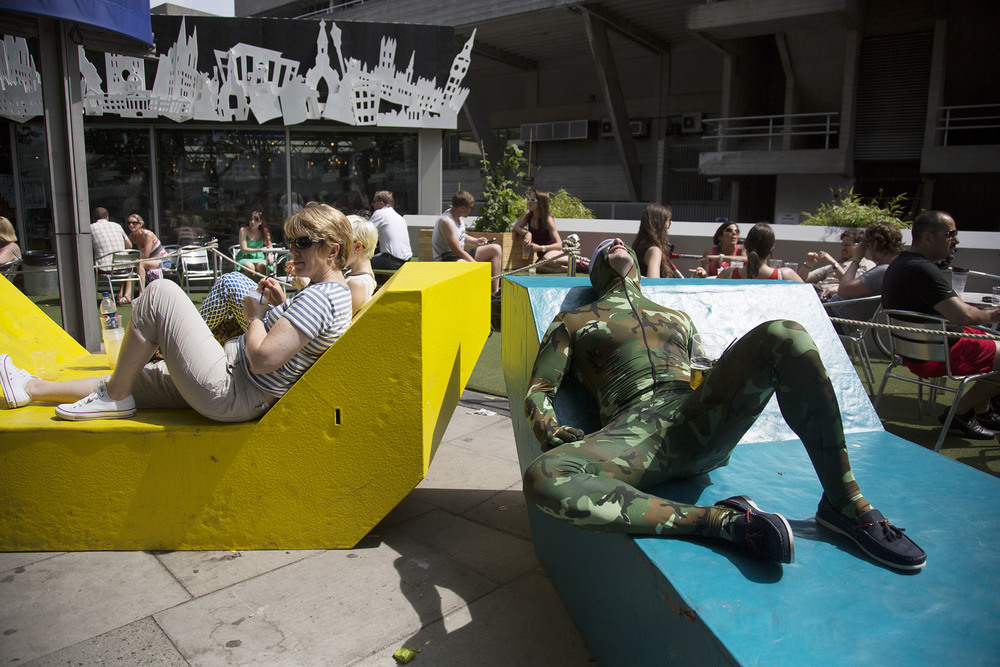 Man on his stag party wearing a camouflage body stocking relaxes on a metal bench.