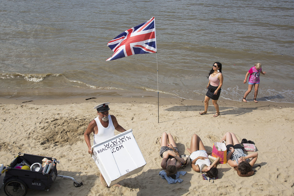 Three girls sunbathing on the River Thames beach on the South Bank.