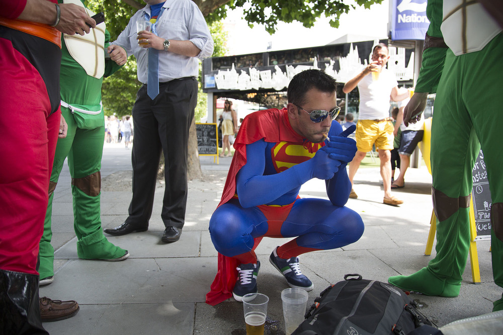 Superman lights up a cigarette near his stag party friends, who are dressed up in superhero costumes.