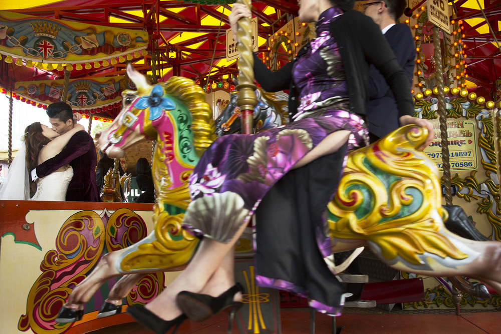 Chinese wedding couple kiss on the South Bank fairground carousel.