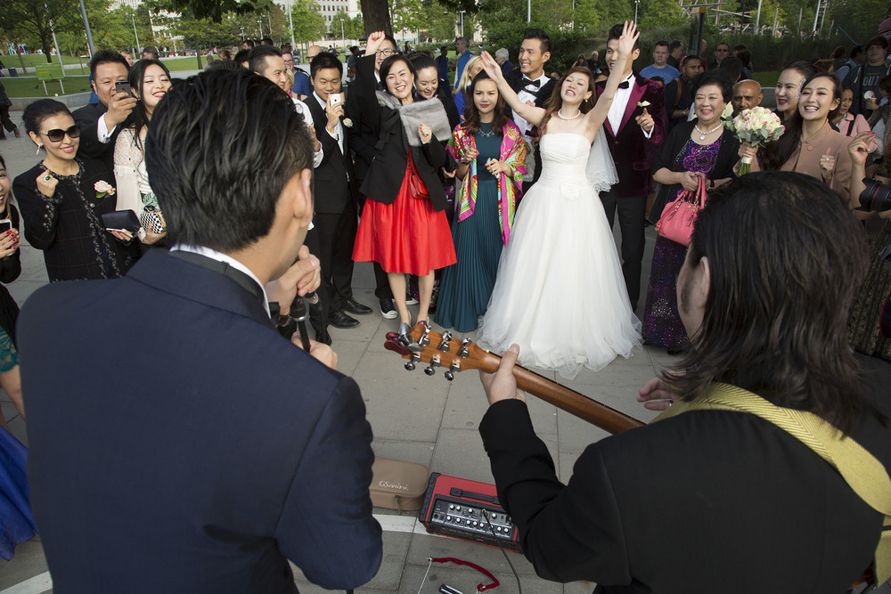 Wedding party guests borrow a busker's guitar and microphone to sing a well known Chinese song to the thrilled couple.