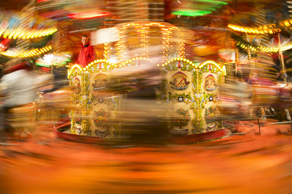 The operator on the carousel fairground ride amidst the blur of movement.