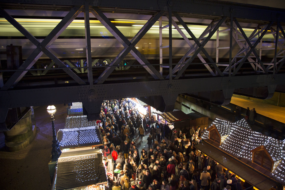 Huge crowds gather at the Christmas market along as a train passes over Hungerford Bridge.