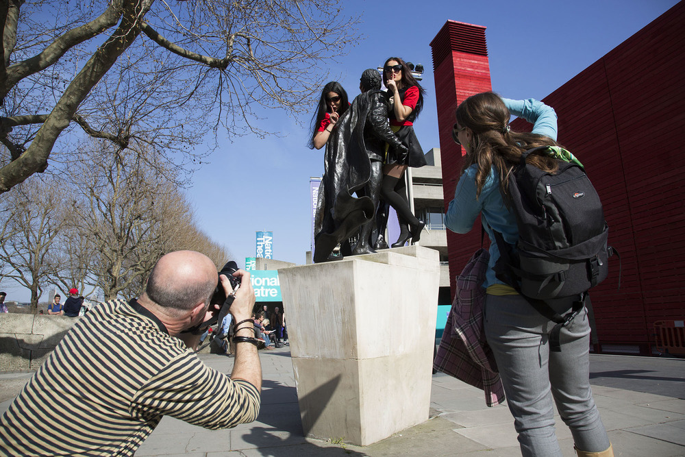 Two models wearing Deborah Azzopardi outfits are photographed on the statue of Sir Laurence Olivier.