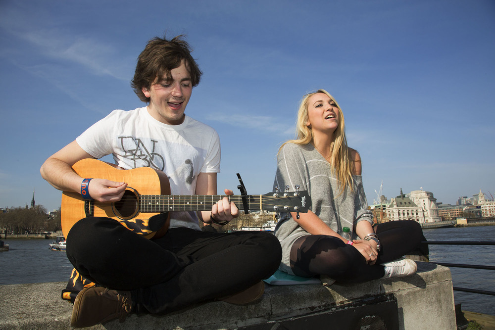 Two young buskers singing and playing guitar on the riverside wall.