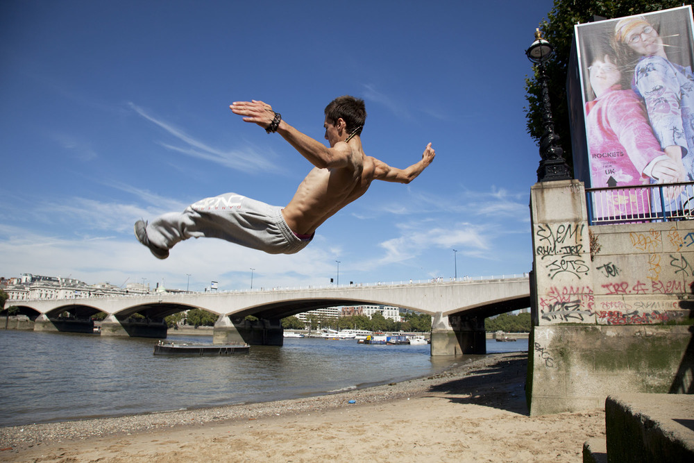 A parkour runner somersaults off the steps down to the beach on the South Bank.