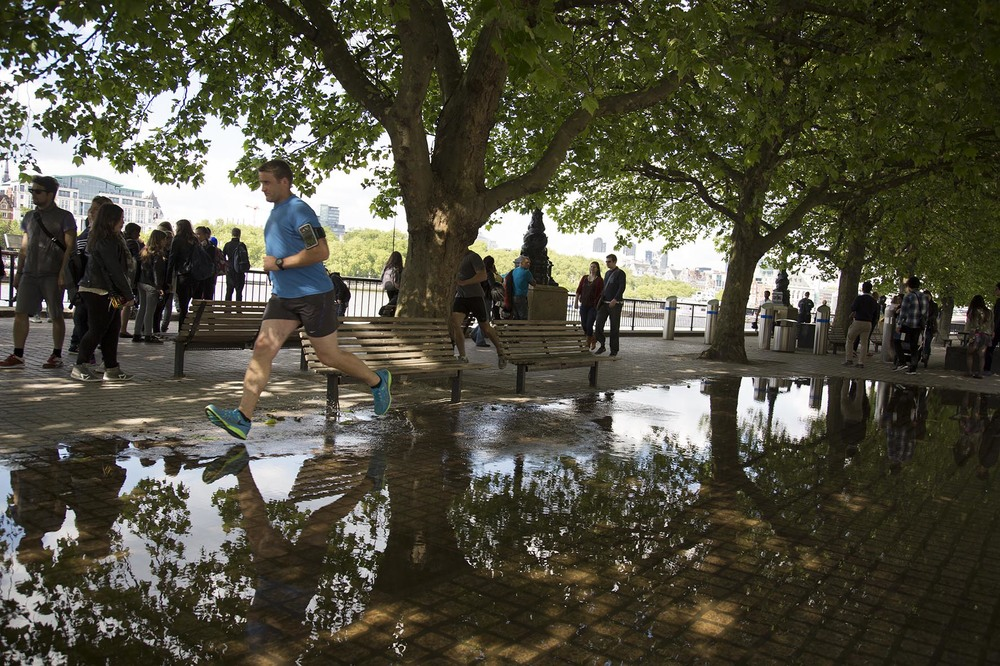 Man running through a large puddle on the riverside walkway.