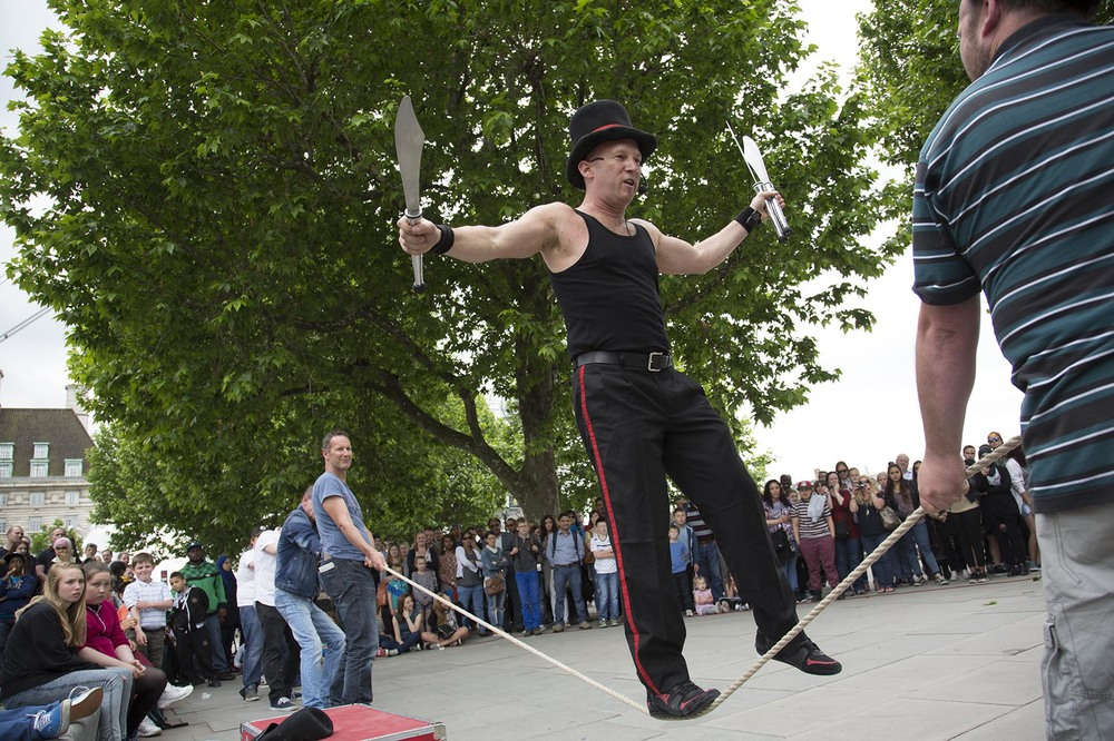 Tight rope walking knife juggling street performance.