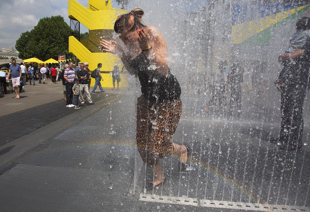 Woman egged on by her friend, takes the plunge to exit the Appearing Rooms fountains.