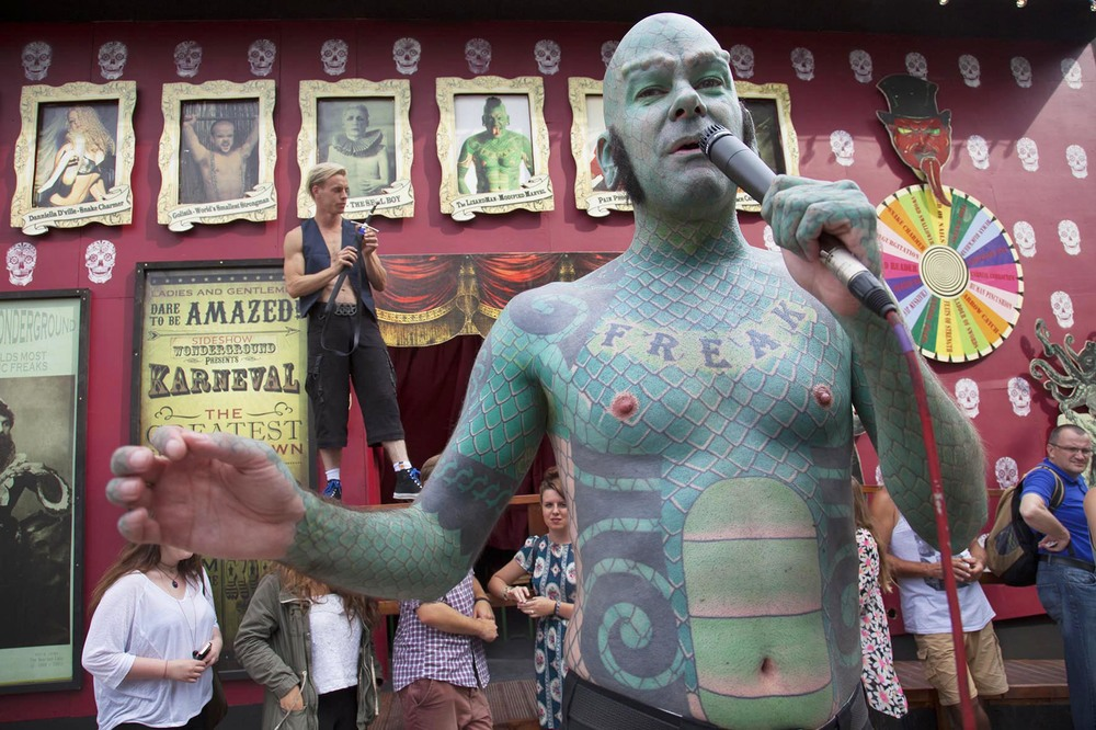 The Lizard Man introduces acts and sells the show 'on the inside' at Wonderground Sideshow freak show.