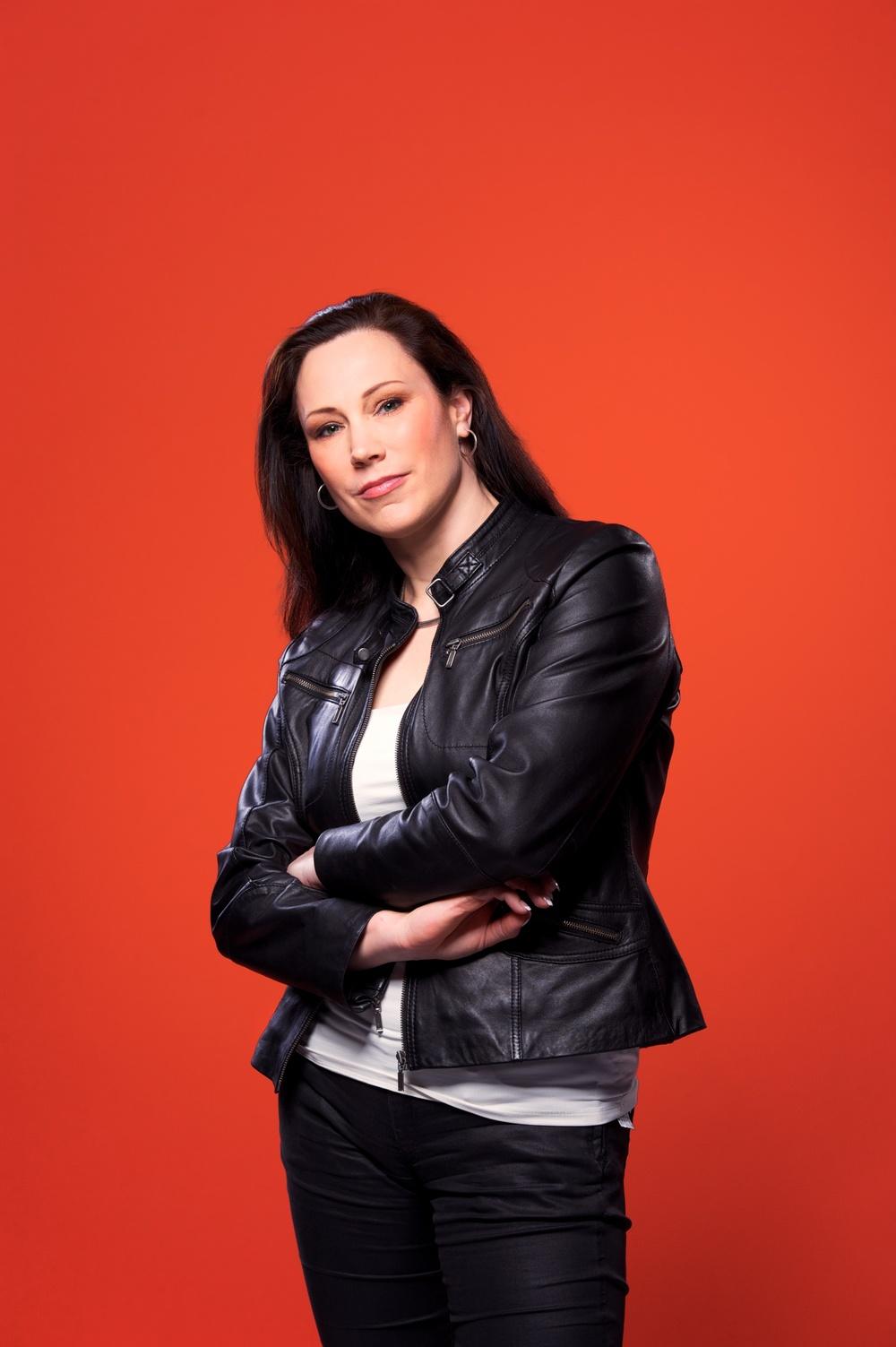 Pressbild på Annika Lidne mot orange bakgrund ©Tobias Björkgren