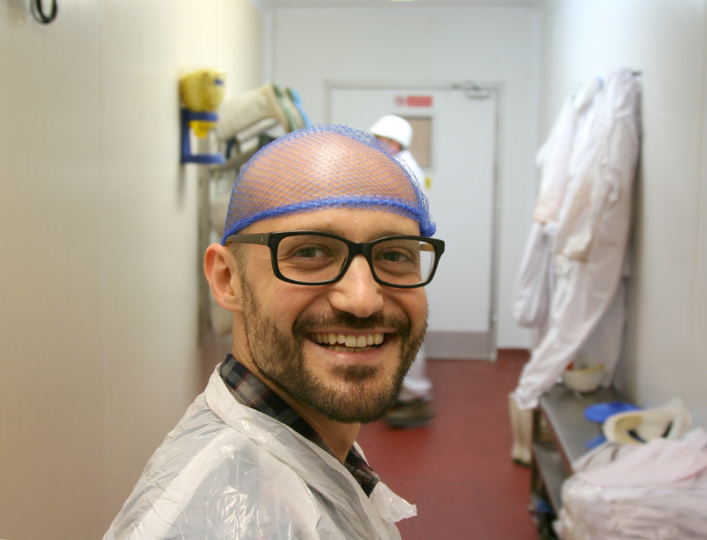 Alessandro, obviously pleased by his plastic coat & 'hairnet', entering the butchery.