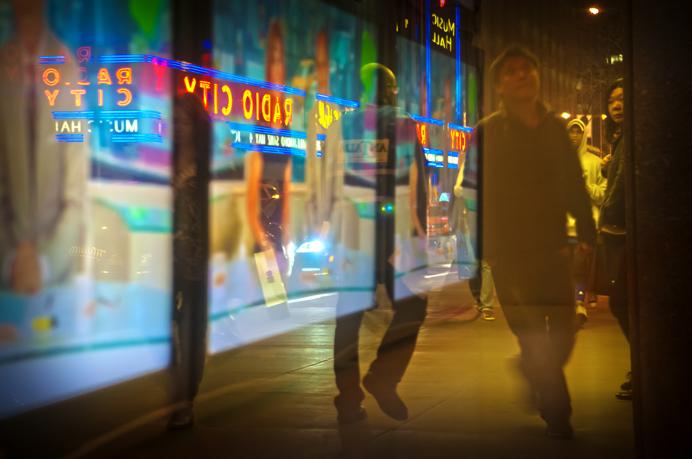 2013.04.24 – New York City, NY – A window across 50th street from Radio City Music Hall reflects pedestrians and the theater's neon lights.